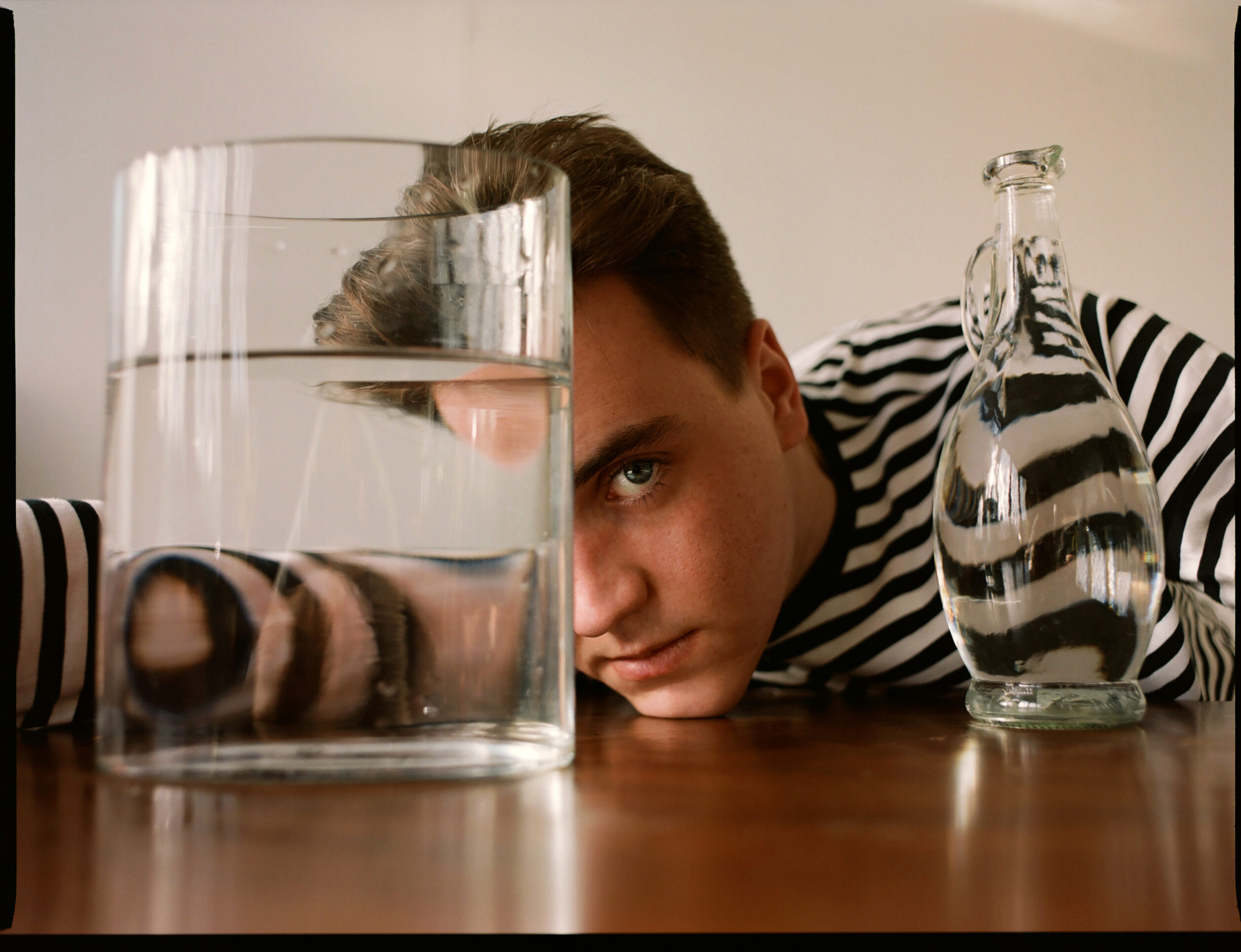 Author Tommy Sissons looks at the camera through a glass of water